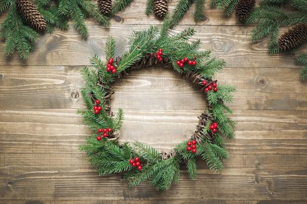 Świąteczny wieniec z gałązek świerkowych z ostrokrzewem na desce