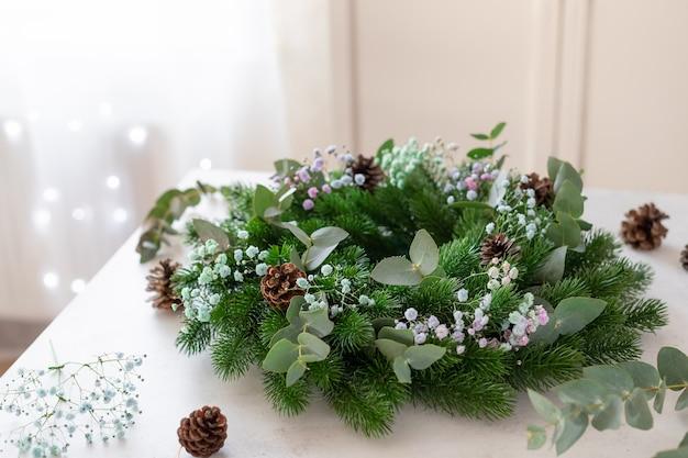 Świąteczny wieniec z gipsówki eukaliptusowej i szyszkami na stole świąteczny wystrój własnoręcznie zrobiony