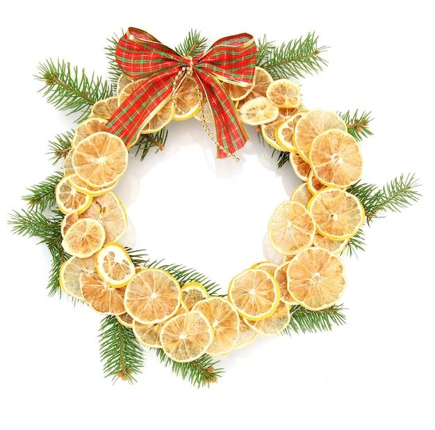 Świąteczny wieniec z suszonych cytryn z jodłą i kokardą na białym tle