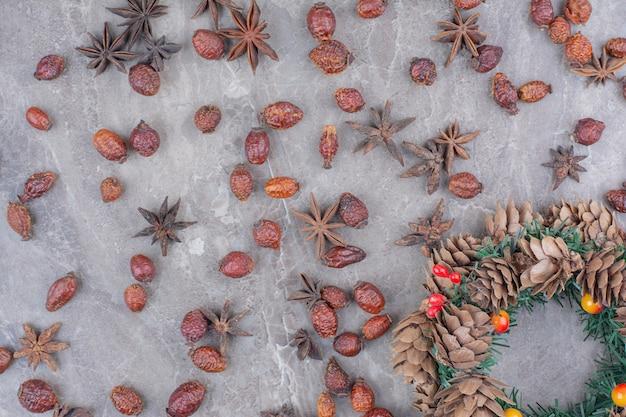 Świąteczny wieniec z szyszek i anyżu gwiazdkowatego na tle marmuru.