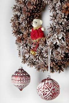 Świąteczny wieniec z szyszek świąteczne zabawki ze szkła i misia
