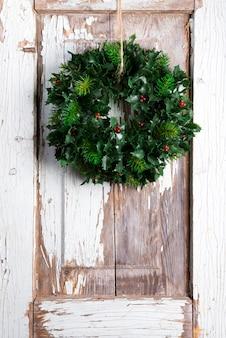 Świąteczny wieniec z zielonych liści i jagód ostrokrzewu roślina na tle starych drewnianych drzwi