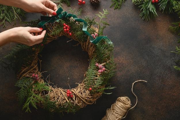 Świąteczny wieniec ze świeżej naturalnej gałęzi świerkowej z czerwonymi jagodami na brązowym tle nowy rok xmas