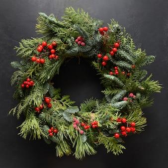 Świąteczny wieniec ze świeżej naturalnej gałęzi świerkowej z czerwonymi jagodami nowy rok święta bożego narodzenia