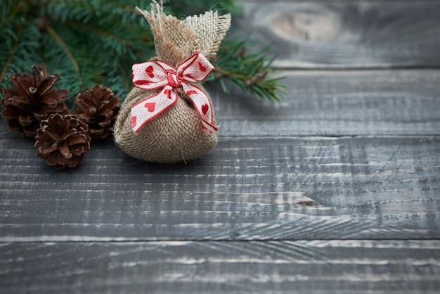 Świąteczny worek z małym prezentem na drewnie