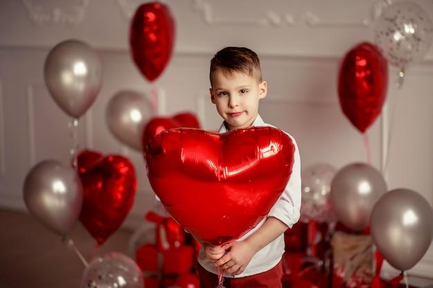 Świąteczny wystrój na urodziny lub walentynki. przewiewne szare metaliczne balony i konfetti. wesoły dziecko chłopiec trzyma w ręku czerwony balon w kształcie serca