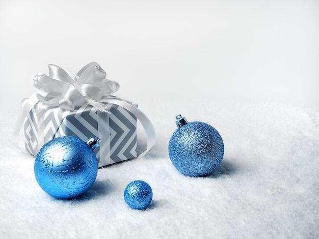 Świąteczny wystrój. niebieskie bombki i pudełko z białą kokardką
