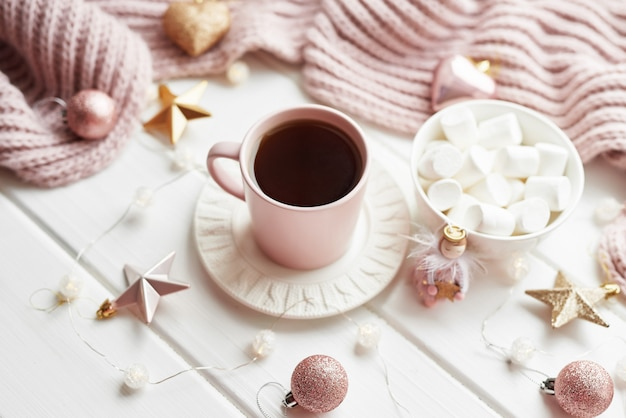Świąteczny wystrój, piłki, wełniana krata na oknie, koncepcja komfortu w domu, sezonowe zimowe uroczystości. . świąteczna różowa filiżanka z pianką.