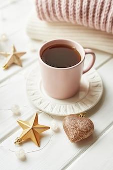 Świąteczny wystrój, piłki, wełniana krata na oknie, koncepcja komfortu w domu, sezonowe zimowe uroczystości. . świąteczny różowy kubek