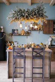 Świąteczny wystrój w kuchni. boże narodzenie naczynia kuchenne. jasne wnętrze noworocznej kuchni. kuchnia jest miętowo-niebieska.