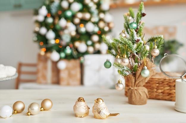 Świąteczny wystrój w kuchni. świąteczne zastawy stołowe. świąteczne przybory kuchenne. jasne wnętrze kuchni noworocznej. szablon karty nowego roku. choinka w kuchni.