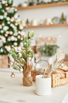Świąteczny wystrój w kuchni. świąteczne zastawy stołowe. świąteczne przybory kuchenne. jasne wnętrze kuchni noworocznej. szablon karty nowego roku.