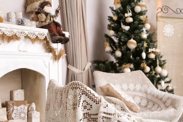 Świąteczny wystrój w naturalnych beżowych kolorach, sztuczny kominek z prezentami, dwa fotele i udekorowane choinki.