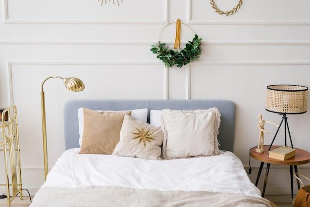 Świąteczny wystrój w sypialni. łóżko z poduszkami, nad łóżkiem wianek