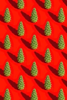 Świąteczny wzór z zieloną szyszką i ciemnym cieniem na czerwonym tle