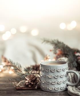 Świąteczny z filiżanką na drewnie ze światłami i świątecznym wystrojem. przytulność i wygoda w domu