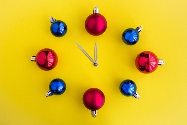 Świąteczny zegarek z jasnych kulek pośrodku żółtej powierzchni. widok z góry. skopiuj miejsce.
