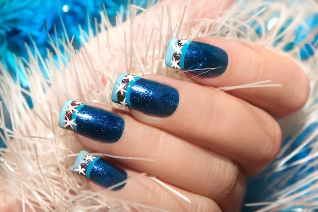 Świąteczny zimowy niebieski wzór francuski manicure z płatkami śniegu na końcach paznokci.