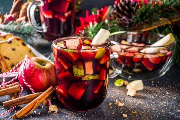 Świąteczny zimowy poncz owocowy lub napój sangria. boże narodzenie grzane czerwone wino. koktajl ponche de frutas navideño, meksykański gorący napój świąteczny z trzciną cukrową i owocami, gorący napój winny z słodkiego likieru