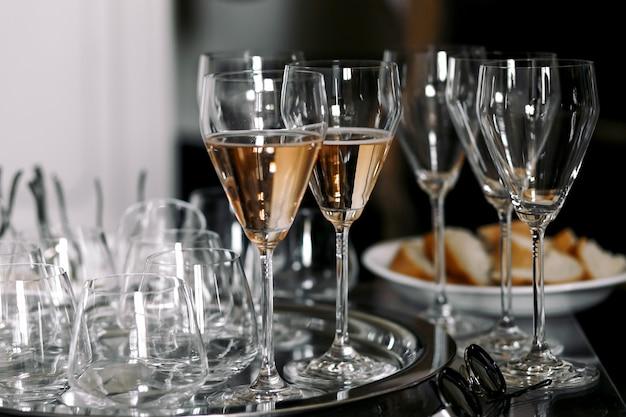Światła dzienne błyszczą nad fletami z szampanem