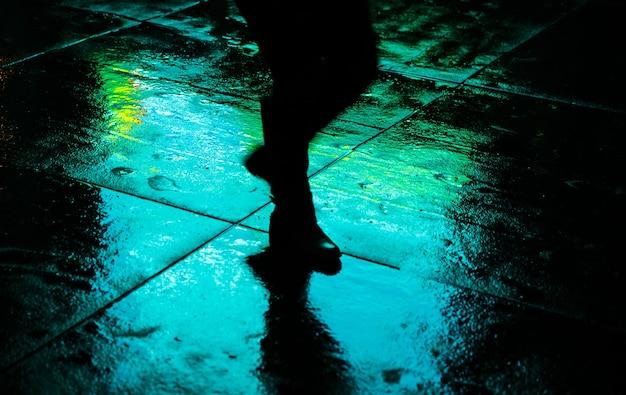 Światła i cienie nowego jorku. nieostrość obrazu ulic nowego jorku po deszczu z odbiciami na mokrym asfalcie. sylwetki ludzi chodzących na ulicy