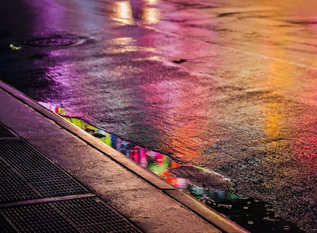Światła i cienie nowego jorku. ulice nowego jorku po deszczu z odbiciami na mokrym asfalcie. sylwetki ludzi chodzących na ulicy