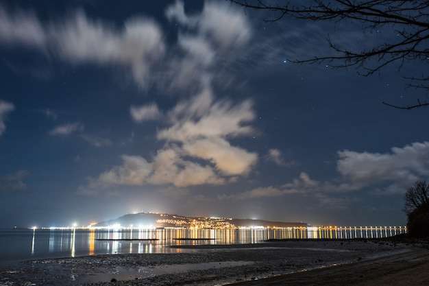 Światła miasta i nocne niebo z plaży sandsfoot w dorset w wielkiej brytanii