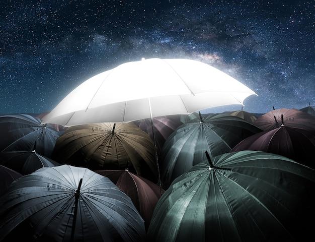 Światła parasol świecące wyróżniające się z tłumu ciemny parasol