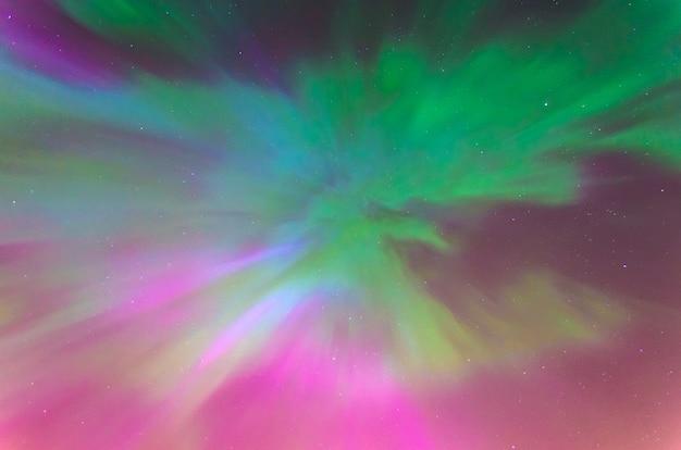 Światła polarne aurora borealis na nocnym gwiaździstym niebie, faktura i wielobarwne zjawiska naturalne.