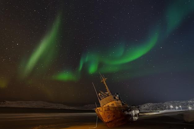 Światła polarne na rozgwieżdżonym niebie. kuter rybacki leżący na boku. teriberka, rosja