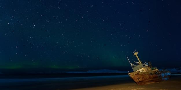Światła polarne na rozgwieżdżonym niebie kuter rybacki leżący na brzegu morza barentsa teriberka rosja