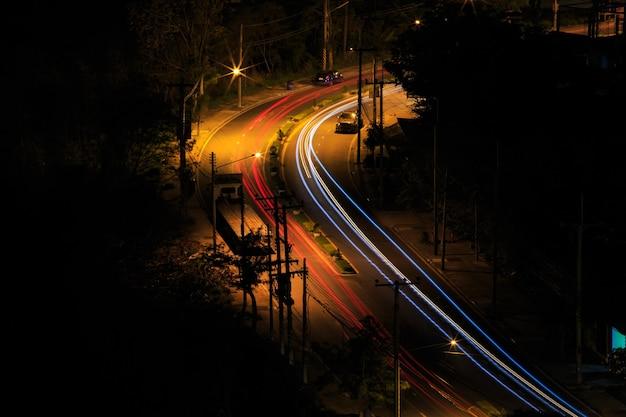 Światła samochodów na drodze. obraz artystyczny. zdjęcie z długim czasem naświetlania zrobione na drodze