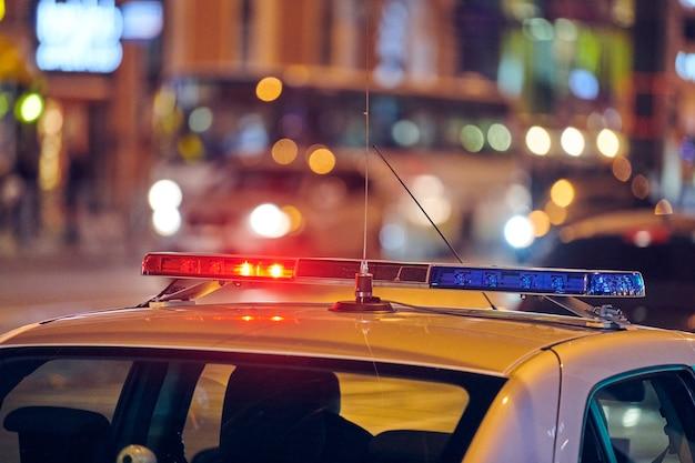 Światła samochodu policyjnego na ulicy miasta w nocy. czerwone i niebieskie światła.