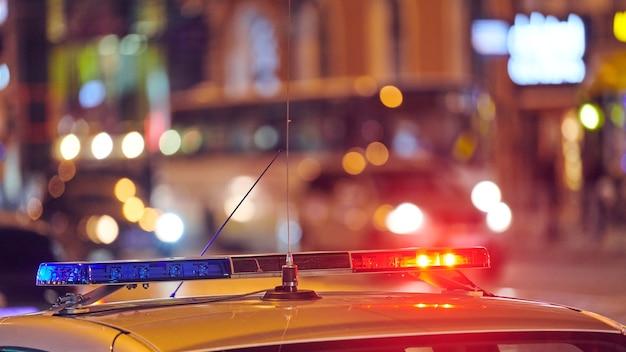 Światła samochodu policyjnego na ulicy miasta w nocy. czerwone i niebieskie światła