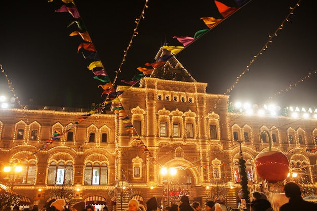 Światła uroczystości i dekoracje na placu czerwonym na świąteczne boże narodzenie i nowy rok. olśniewający żółte światła na fasadowym dziąśle w moskwa, rosja. nocna panorama moskwy