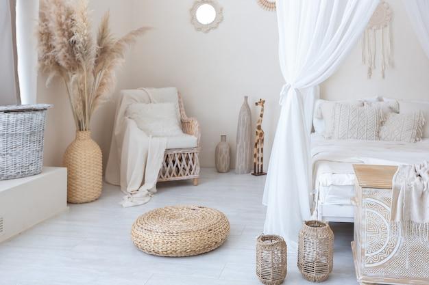 Światło dzienne przez ogromne panoramiczne okno oświetla przytulne orientalne wnętrze pokoju w beżowej kolorystyce z wiklinowymi meblami i autentycznymi elementami