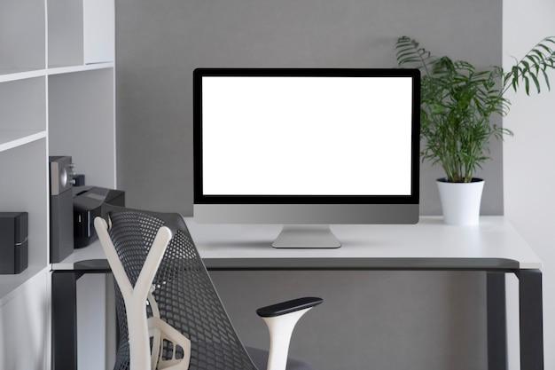 Światło dzienne wnętrze z białym nowoczesnym monitorem komputerowym w biurowym stole, ortopedycznym krześle i doniczce na zieleń