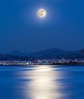 Światło księżyca odbija się na morzu w zatoce miasta palermo (włochy).