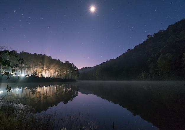 Światło lasu sosnowego świeci wraz z księżycem na zbiorniku o świcie, pang oung, mae hong son, tajlandia