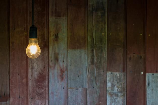 Światło od rocznik żarówki z starym drewna ściany tłem, wizerunek z kopii przestrzenią.