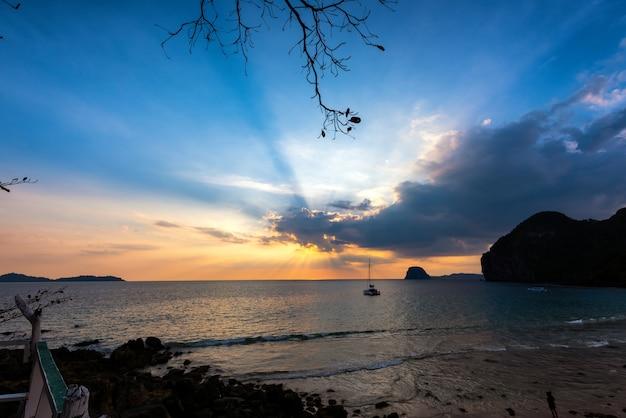 Światło słońca przechodzi przez chmury z jachtem w morzu