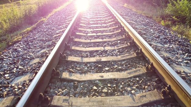 Światło słoneczne i ruch na torach kolejowych. słońce świeci w obiektywie aparatu.