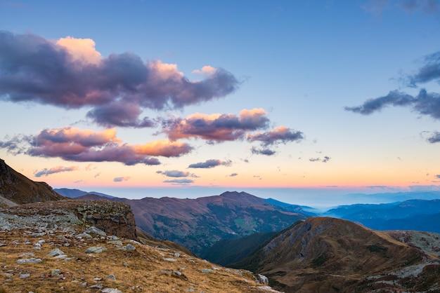 Światło słoneczne na alpejskich szczytach górskich i malowniczych chmurach