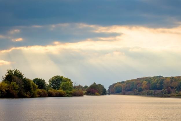 Światło słoneczne przenika przez ciemne chmury nad rzeką, rzeką i lasem w oddali z malowniczym niebem