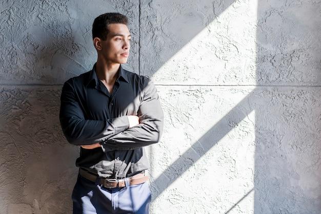 Światło słoneczne spada nad poważną młody człowiek pozycją przeciw betonowej ścianie