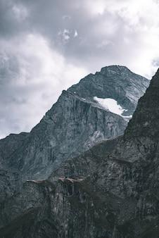 Światło słoneczne w alpejskiej dolinie ze świecącymi szczytami górskimi i malowniczymi chmurami. włoskie alpy francuskie, letni cel podróży, stonowany obraz, vintage filtr, podzielony ton.