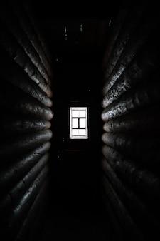 Światło słoneczne wpadające przez drewniane okno w starym ciemnym pokoju