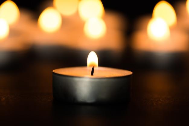 Światło ze świeczki. świeca bożonarodzeniowa płonąca w nocy. świeca streszczenie tło.