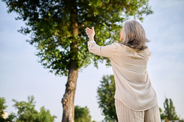 Światopogląd. siwowłosa kobieta w lekkich ubraniach z uniesionymi rękami stojąca przed drzewem z plecami do aparatu w parku w słoneczny dzień