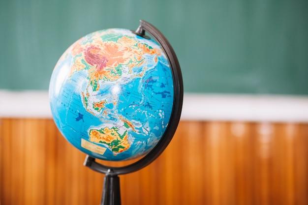 Światowa kula ziemska w sala lekcyjnej na zamazanym tle